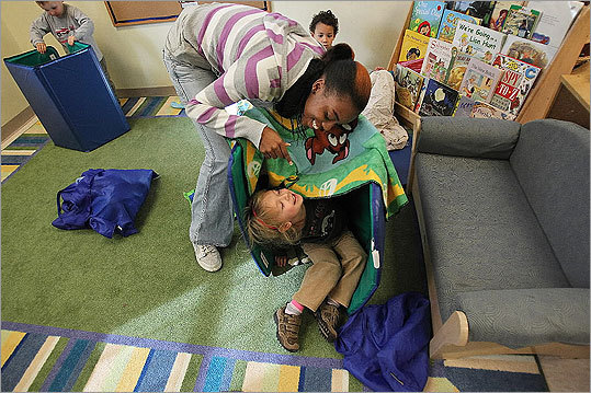 Chayla Smith, a preschool teacher, gets kids ready for nap time at Bright Horizons in Watertown.