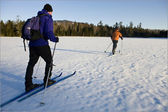 From Maine to the Adirondacks, backcountry skiers enjoy the freedom from lifts and crowded slopes. Above: skiers cross a frozen pond near Greenville, Maine.