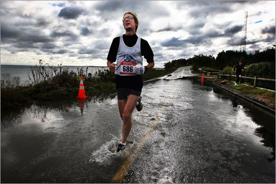 JOSEPH ALFANO, 45, of Holden, running a flooded course in the Cape Cod Marathon, Oct. 30, 2011 -- 'The Cape Cod Marathon is a hard race. It's got a lot of hills. It was a windy day right after the big storm but also very beautiful. When I saw the flooded road, it was not a big deal. You're about 3 miles out. I thought, 'Come on, you've made it this far, you've got to keep running. You can't go around it, you've got to get your feet wet.' You've got to go a little crazy if you run a marathon. I'd rather go straight for the finish line and not waste two steps than stay dry. I needed to run it in 3:25 to qualify for Boston, and I ran it under 3:20. It worked out.'