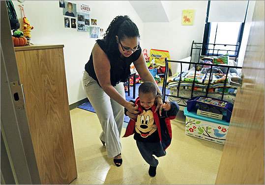 The program, which started in 1993, is designed for a maximum of 10 students, men or women. This year it is serving eight mothers and their children, ages 10 1/2 months to 4 years. Pictured: Student and mother Mariel Margarin (left) helps her three year old son Damien with his jacket in his bedroom as they are about to head out of their dorm building to the playground that is behind the building.