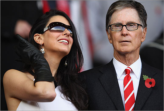 Linda Pizzuti Pizzuti (pictured, left) is the wife of Boston Red Sox owner John Henry (pictured, right). This photo of the couple was taken at a Barclays Premier League match between Liverpool (which Henry owns) and Swansea City.