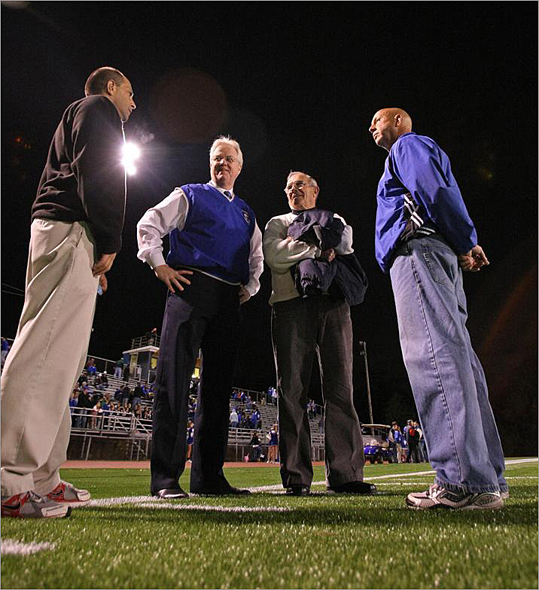 Town and school officials dedicated the high school's new all purpose turf field during the halftime of the Braintree-Natick football game. Before the game, Athletic Director Mike Denise ,left, meets with former coaches, from left: David Swanton (current headmaster), Edwin Beck, and right, Frank Tricomi all standing on new turf.