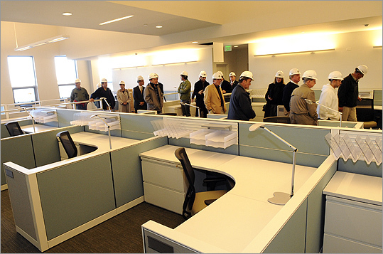'This was her last project,' L'Heureux said. 'Her design is a tribute to her skills and the sensitivity she felt for Salem as a community.' Pictured: A group of Salem, MA city councilors and others tour offices for the district court clerk magistrates.
