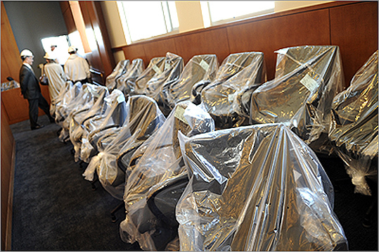 Pictured: Chairs in a jury box are covered in plastic in a courtroom .