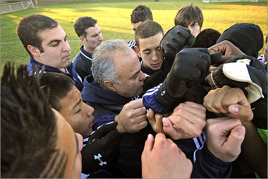 The Mustangs of Medford High School proudly charged onto the soccer field after saving coach Mike Petrides's job last summer. It was a season of learning on and off the soccer pitch. At left, Medford head coach Mike Petrides (center) joined fists with his team before the start of the tournament game against Chelmsford.
