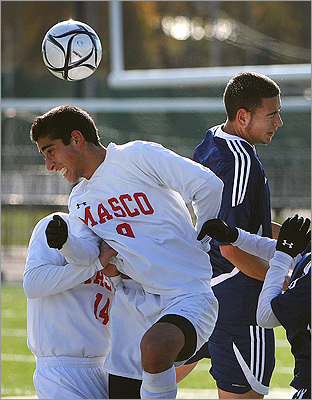 More than champions, Petrides said he wants his players to grow up to be good men. 'I tell them, 'Education and family first, then soccer' ' he said. Pictured: Masconomet's Keeyon Olia (left) and Medford's Pires battle for the ball during the state tournament.