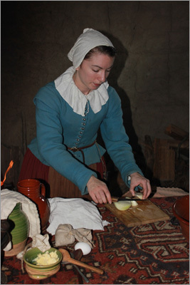 A colonist prepared vegetables for a traditional 17th-century-style dinner. The role players stay in character during your visit, even when modern-day technology enters the homes to document the museum.
