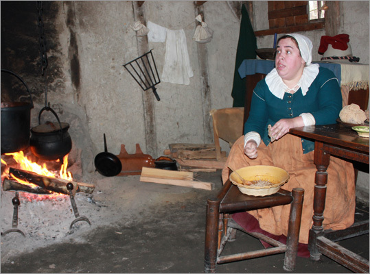 A colonist made bread pudding while answering questions from visitors who had entered her home.
