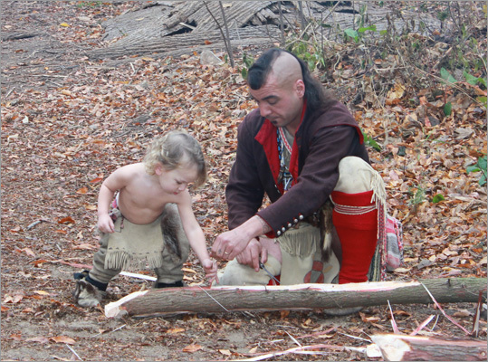 In the nearby Wampanoag Village, a Wampanoag splicing tree limbs for his hut shows the craft to his young son.