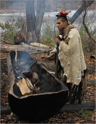 Here, a Wampanoag displayed the act of burning out a tree trunk in order to create a canoe. The fire will remove the sap from the tree and create a hardened surface suitable for navigating the nearby waterways.