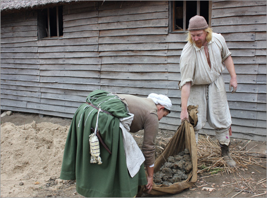 The village recreates some of the homes and gardens that would have existed in the original Plymouth town. Here, colonist role players rounded up some clay to be used in building a home's foundation.