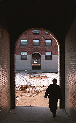 Past 1998: A youth walks through an archway in the project.