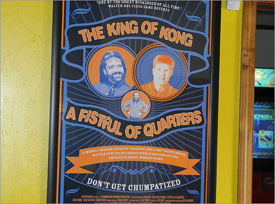 "A marquee poster for the 2007, documentary-style film ""The King of Kong: A Fistful of Quarters"" hangs on a wall inside ACAM. The film centered around the Funspot tournament, specifically the fight for the world record in Donkey Kong between a soft-spoken, up-and-coming player from Washington State named Steve Weibe, and a cocky, long-time Donkey Kong champion, Billy Mitchell of Florida. Read the Boston.com article."