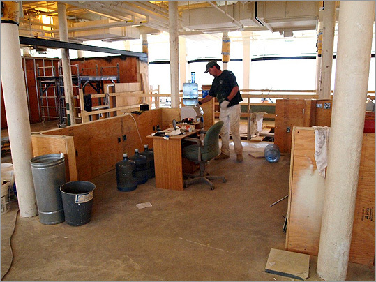 A worker gets a cup of water in the area that will become the visitors' center desk. The area around the desk will include interpretive exhibits, an audio-visual orientation program for all 16 sites on the Freedom Trail, and iPad kiosks for accessing information.
