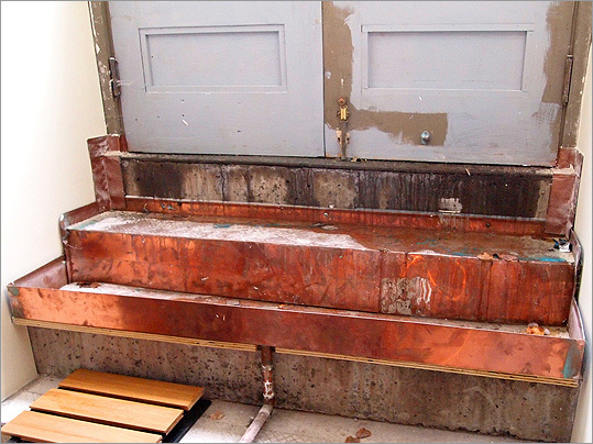 Copper basins were fashioned to capture rainwater seepage around unused bulkhead doors added to the basement during an earlier renovation.