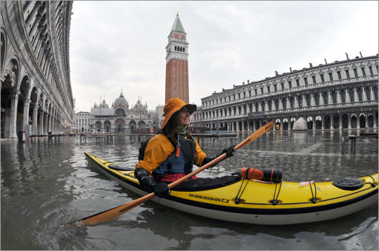 A woman steered her kayak on the flooded Piazza San Marco (St Mark's square) during the first 'acqua alta' of the season in Venice. The 'acqua alta', is a convergence of high tides and a strong sirocco.