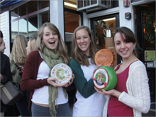 "Cheese Shop employees passed samples of Crucolo cut from the wheel once Lovis used a wire to halve the giant cheese, then cut it into successively smaller pieces to hand out. He also served cheese balls with ""stick,"" or a spicy ham inside. Crucolo dancers from Concord Academy (left to right) Gracie Mason-Brown, Sarah Eberth and Ellie New."