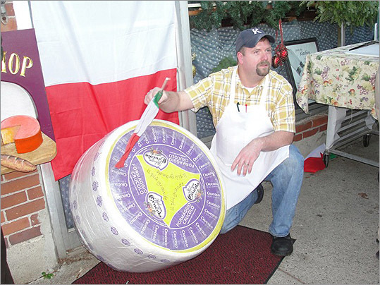 "The selectmen designated it ""Crucolo Day in Concord."" A man strolled down Walden Street crooning Italian songs. Students from Concord Academy danced on the sidewalk. Families flocked to the Milldam to hail the arrival of a 400-pound wheel of Crucolo cheese at the Concord Cheese Shop on Thursday. Cheese Shop staffer Justin Kopacz poses with the wheel of Crucolo before it is cut."