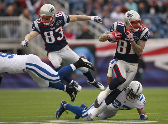 Patriots tight end Aaron Hernandez evaded a tackle by Colts cornerback Jacob Lacey (27) in the first quarter. Receiver Wes Welker is at left.