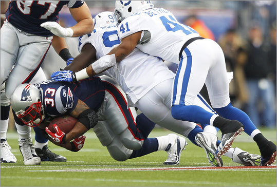 Faulk was brought down by the Colts' Mario Addison (center) and Antoine Bethea (right) in the first quarter after a 2-yard gain.