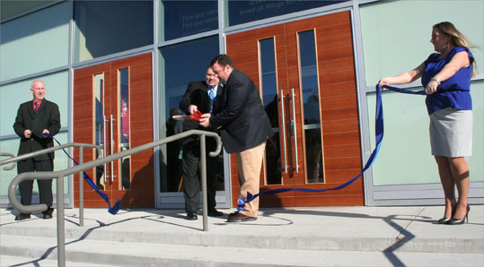 Braintree Town Councilor Sean Powers cuts the ribbon outside of the restaurant with General Manager Derek Robinson. 'I think it will take some time [for everyone to be on board],' Powers said. 'The finished product still needs to be introduced to the neighborhood and to the town.'