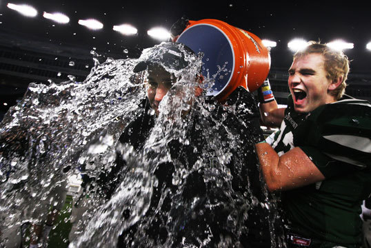 DAVE MAIMARON, Duxbury High School coach, getting doused with ice water by junior linebacker RON KOSHAREK after the team concluded its second consecutive undefeated season with a 35-0 victory over Tewksbury in the Division 2 Super Bowl, at Gillette Stadium in Foxborough, Dec. 3, 2011. Maimaron -- 'Yeah, I knewit was coming. I brought an extra set of clothes just in case. I took off my headset and gave someone my wallet and my phone. The water was cold and wet. I'mgetting used to it, two years in a row. The senior class won us a lot of football games and we are going to miss them. It's been awesome.' Kosharek -- 'To be honest, words can't describe how happy I was. Going undefeated two seasons in a row is indescribable. I just want to give credit to the seniors for a tremendous season and our coaching staff, who put in more hours, I think, than some college programs. It was a direct hit on him. It was freezing. I can't imagine how he felt when he got showered. I was thinking, 'Let's go home and have a good time.''
