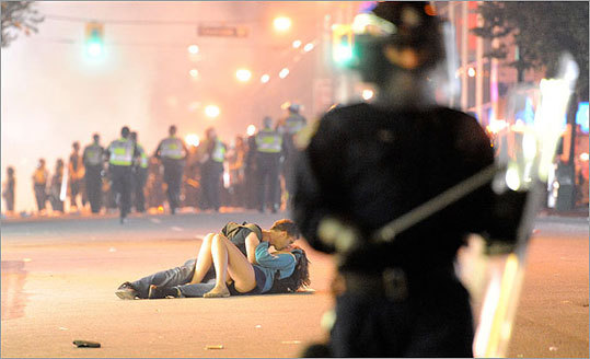 A bizarre and intriguing photograph emerged from the violent scenes of downtown Vancouver that played out in the hours after the Boston Bruins defeated the Canucks to win the Stanley Cup. The photo showed a young couple lying down together on the street engaged in a passionate kiss, as riot police in the foreground and background of the photo tried to control the chaos.