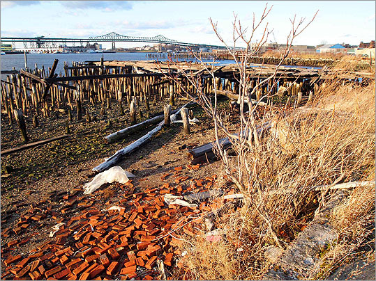 This large lot between Border Street and Boston Harbor overlooks the revitalized Charlestown Navy Yard and, as seen at left, the Tobin Bridge, but is overgrown and filled with construction debris, household trash, and rotting piers.