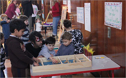 Along with the magic show and holiday crafts, children at the event tried their hand at games. These boys were trying to knock down pins with a spinning dreidel.