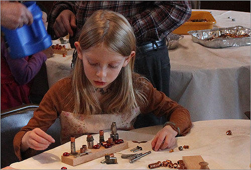 Gemma Conway, 7, of Arlington was making a menorah out of wood, nuts, and pieces of pipe for her grandparents.