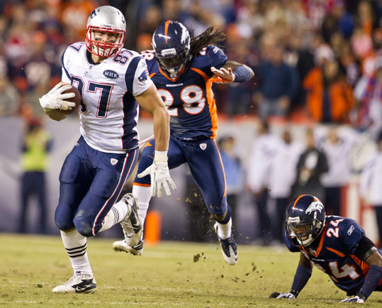 Patriots tight end Rob Gronkowski picking up extra yardage after the catch as Broncos Quinton Carter (No. 28) and Champ Bailey try to catch him during fourth quarter action.