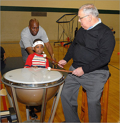 The recreation center, which shares space with Madison Park High School, features two gymnasiums, a swimming pool, football field, dance studio, tennis courts, teen center, running track, a workshop training room and other spaces, city officials said. There is also an unused rowing tank that will be repaired and put into use. Pictured: Mayor Menino tries out the drums. The Eloquent Drum and Bugle Corp performed during the ceremony.