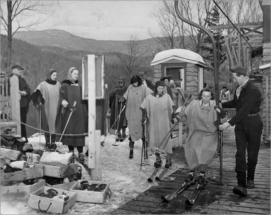 Wearing army ponchos, a group of women lined up to board a lift at Stowe, Vt., on Feb. 15, 1946. The ponchos served as protection against the wind as they rode up the mountain. Upon reaching the summit, the women would remove the ponchos and send them down in the empty chairs.