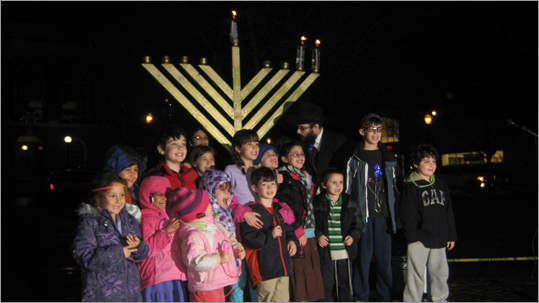 Kids lined up for a picture in front of this year's glowing menorah at the annual lighting ceremony.