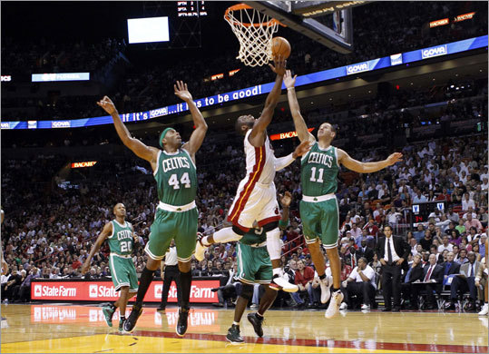 Heat guard Dwyane Wade scored after splitting the defense of Celtics forwards Chris Wilcox (left) and Sasha Pavlovic in the first half.