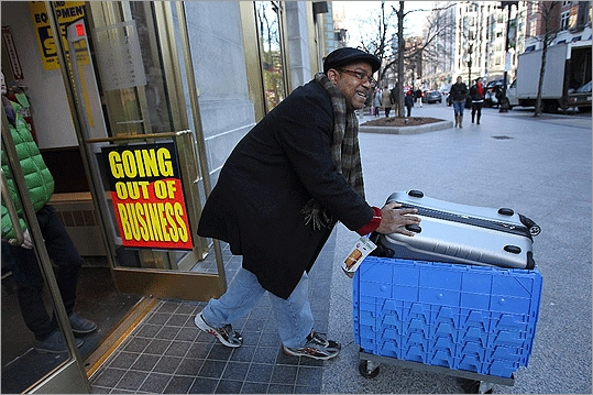 At the store on Boylston Street in Boston, shelves, racks, and display cases were bare of items as shoppers rummaged through the store like treasure hunters. At left, a shopper rolled out his purchases through the door.