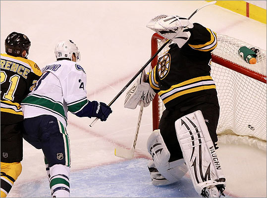 Tim Thomas was hit in the face mask by a high stick from Vancouver Canucks left wing Mason Raymond.