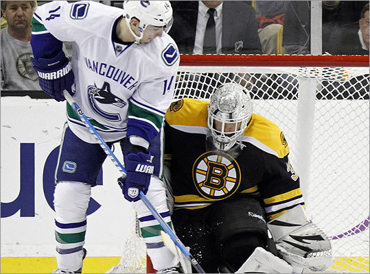 Alex Burrows watched as the puck goes into the net past Tim Thomas in the second period.