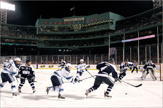 New Hampshire and Maine players took the ice in front of 38,456 at Fenway Park on Sat. night. Here, New Hampshire's Damon Kipp (4) tried to get away from Maine's Joey Diamond (39) during the first period.