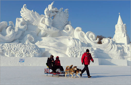 An employee pulled a dog sled carrying tourists in front of a snow sculpture.