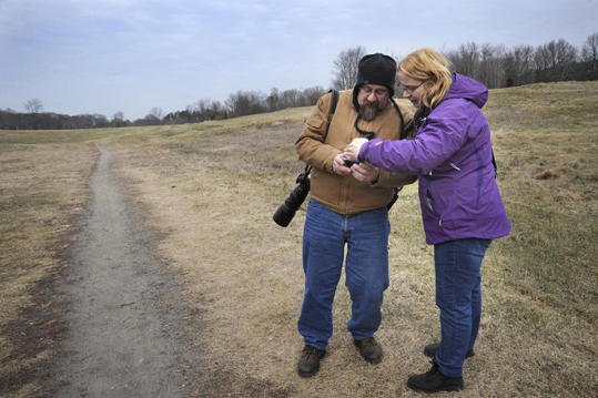 Maguranis often patrols the coyotes' known haunts, such as Rock Meadow, a large conservation area where many residents walk their dogs. He strongly advises residents to keep all dogs leashed during coyote mating season in January and February. Maguranis shows some coyote photos he took to Kristen Donovan (right) at Rock Meadow.