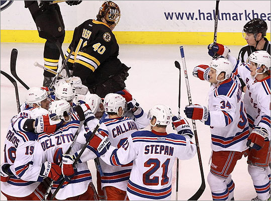 The first-place New York Rangers faced off against the Eastern Conference's No. 2 seed, the Bruins, on Saturday in a game that could very well serve as a playoff primer. Left: Bruins goalie Tuukka Rask skated off the ice as the Rangers celebrated their overtime win.