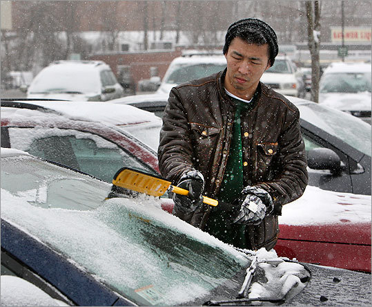 Yuhei Oga, of Somerville, cleared snow from his car in Medford, Mass. Jan. 21, 2012.