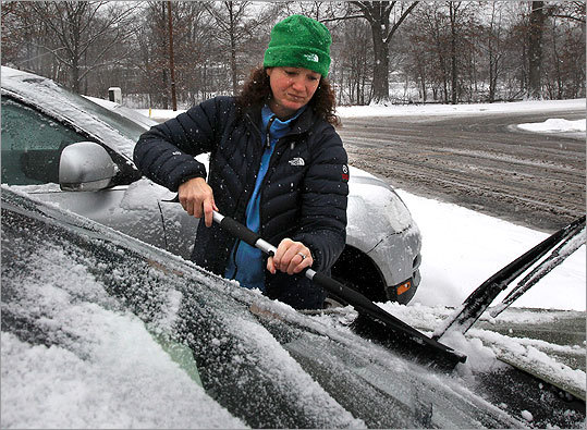 Kim Morris cleared snow from her car at market in Medford, Mass.
