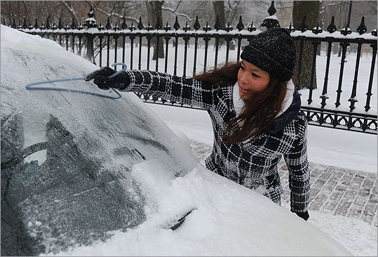 Sang Nguyen, of Charlestown, used a coat hanger to clear the snow off her windshield.