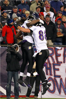 Ravens celebrated with teammate Dennis Pitta after scoring a touchdown in the third quarter against Devin McCourty (not pictured).