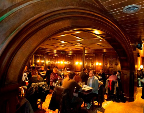 Inside, dark paneling, studded leather chairs, and warm red rugs create an inviting, clubby atmosphere. Saloon boasts a large, elegant bar, but there are many cozy booths and tables if you'd rather not belly up. At left, diners in a room off the bar. The arch in the foreground is 407 years old from a church in England.