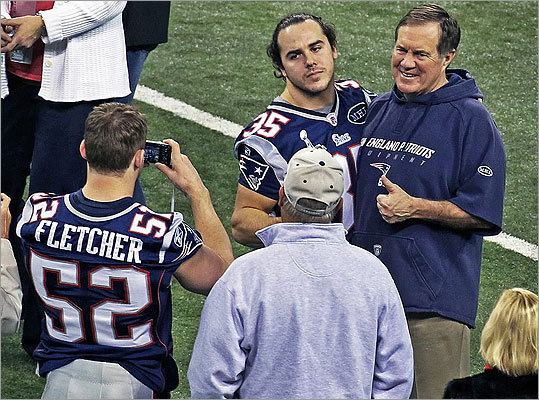 Belichick was all smiles Saturday, posing for photos with individual players and their families. Here he posed with defensive back Ross Ventrone, while linebacker Dane Fletcher took their picture.