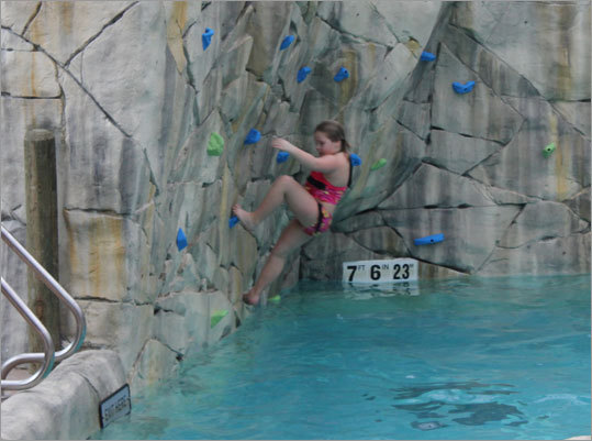 The rock climbing wall is a challenge, and unlike others, this one doesn't require any sort of harness. Slip, fall, or let go, and you simply fall into the pool with a splash.