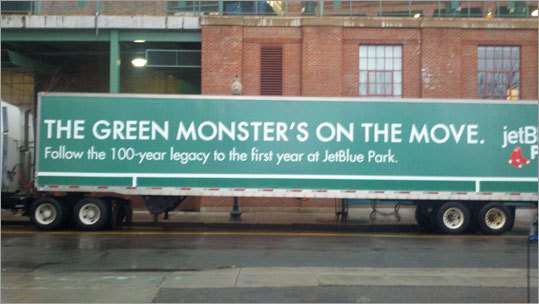 On the side of the truck, the signage says 'The Green Monster's on the move' and 'follow the 100-year legacy to the first at JetBlue Park.'